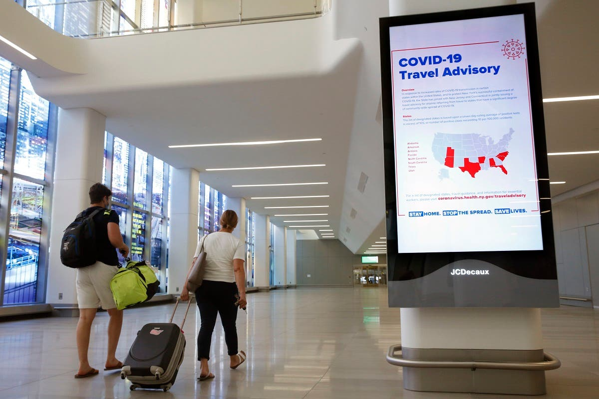 Arriving travelers walk by a sign in the baggage claim area of Terminal B at LaGuardia Airport, on June 25, 2020, in New York. (AP)