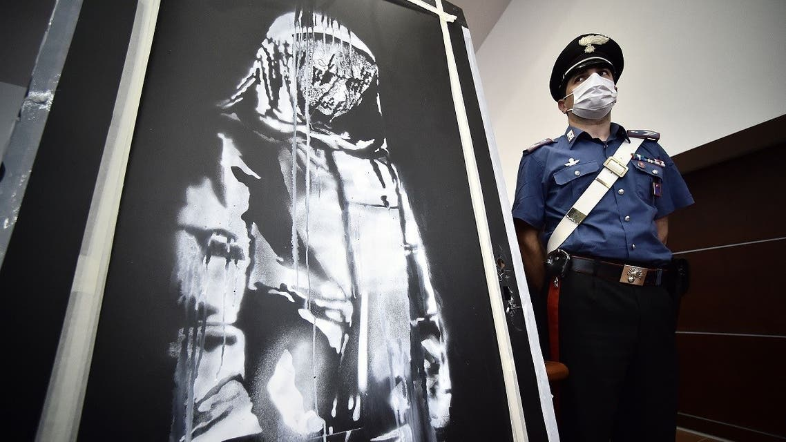 A policeman stands guard near a piece of art attributed to Banksy, that was stolen at the Bataclan in Paris in 2019, and found in Italy, ahead of a press conference in L'Aquila on June 11, 2020. (AFP)