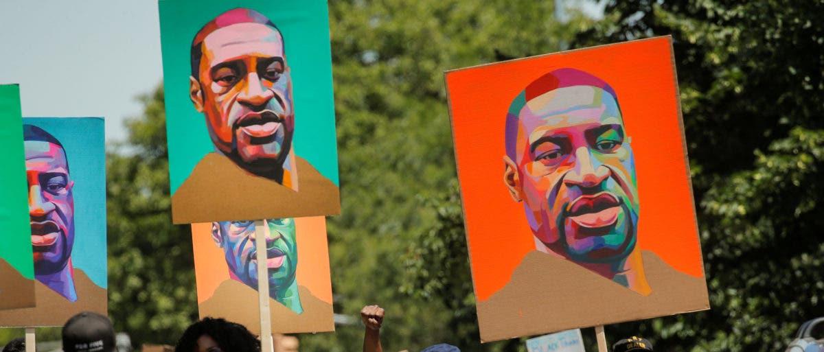 محتجون أميركيون يحملون لافتات بها صور جورج فلويد