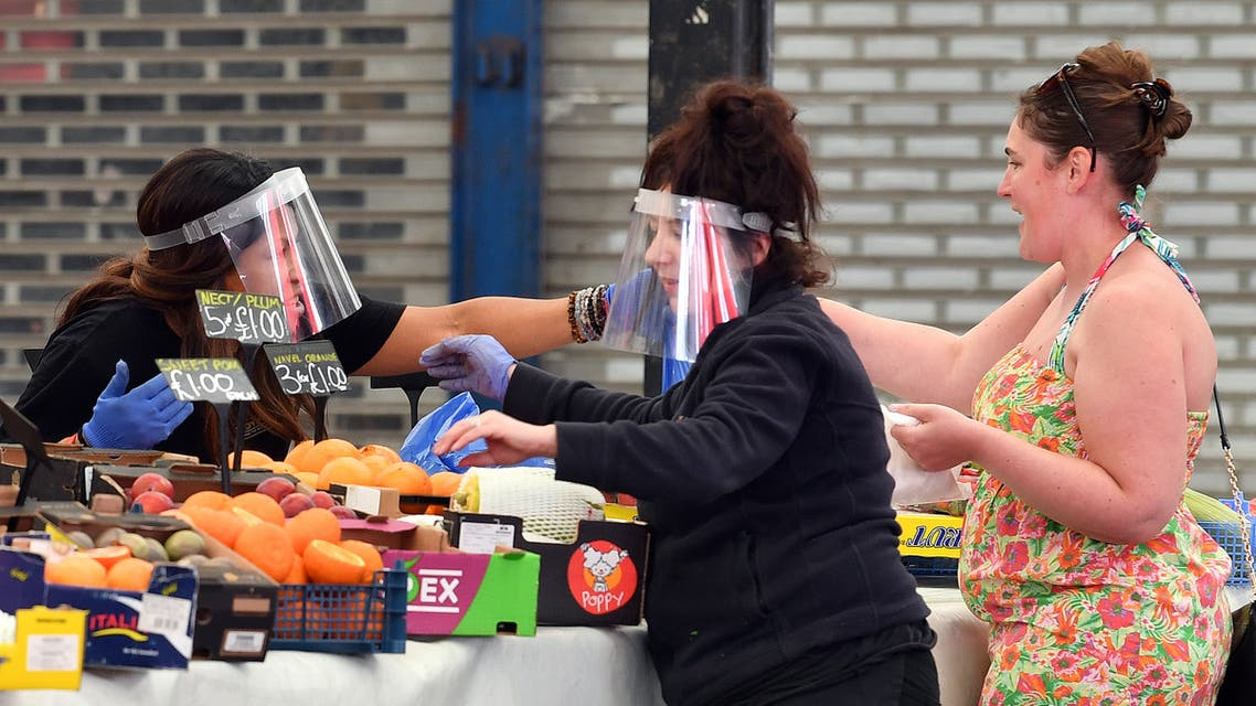 raders wearing PPE (personal protective equipment), including gloves and a visor as a precautionary measure against COVID-19, serve customers at their fruit and vegetable stall at Leicester Market in Leicester. (AFP)