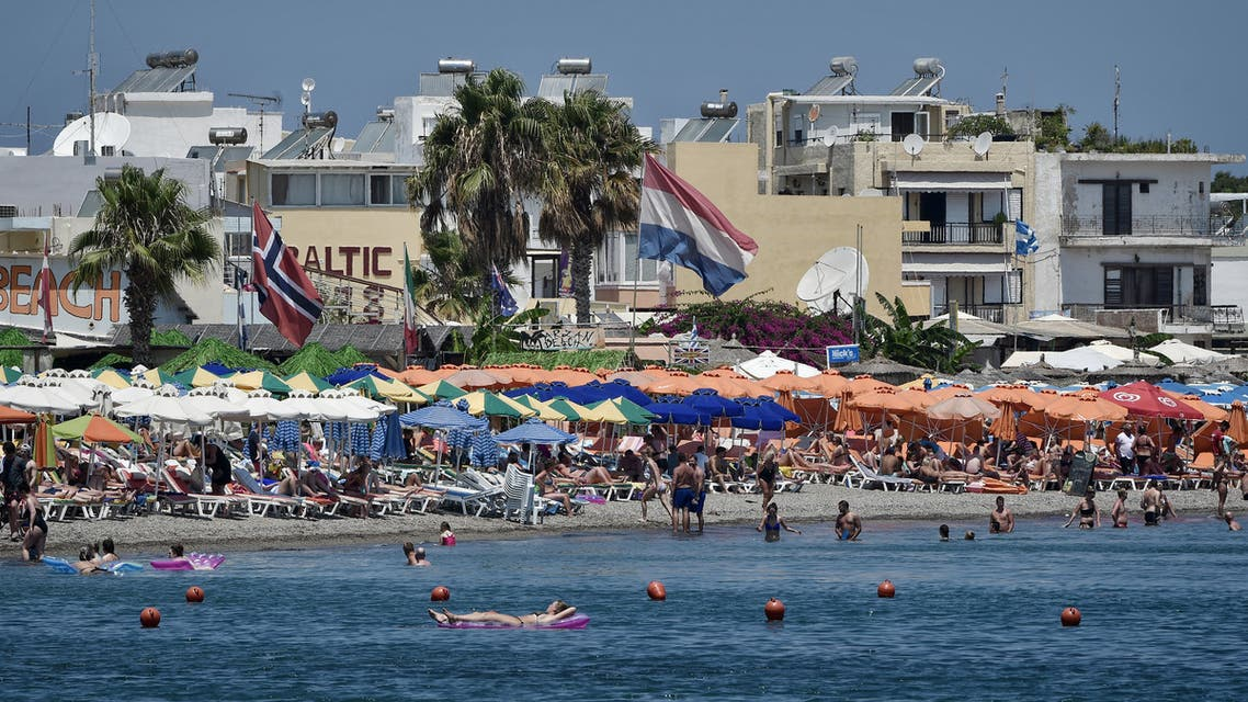 Tourists enjoy the sun and sea on a beach on the Greek Island of Kos on July 22, 2017. (AFP)