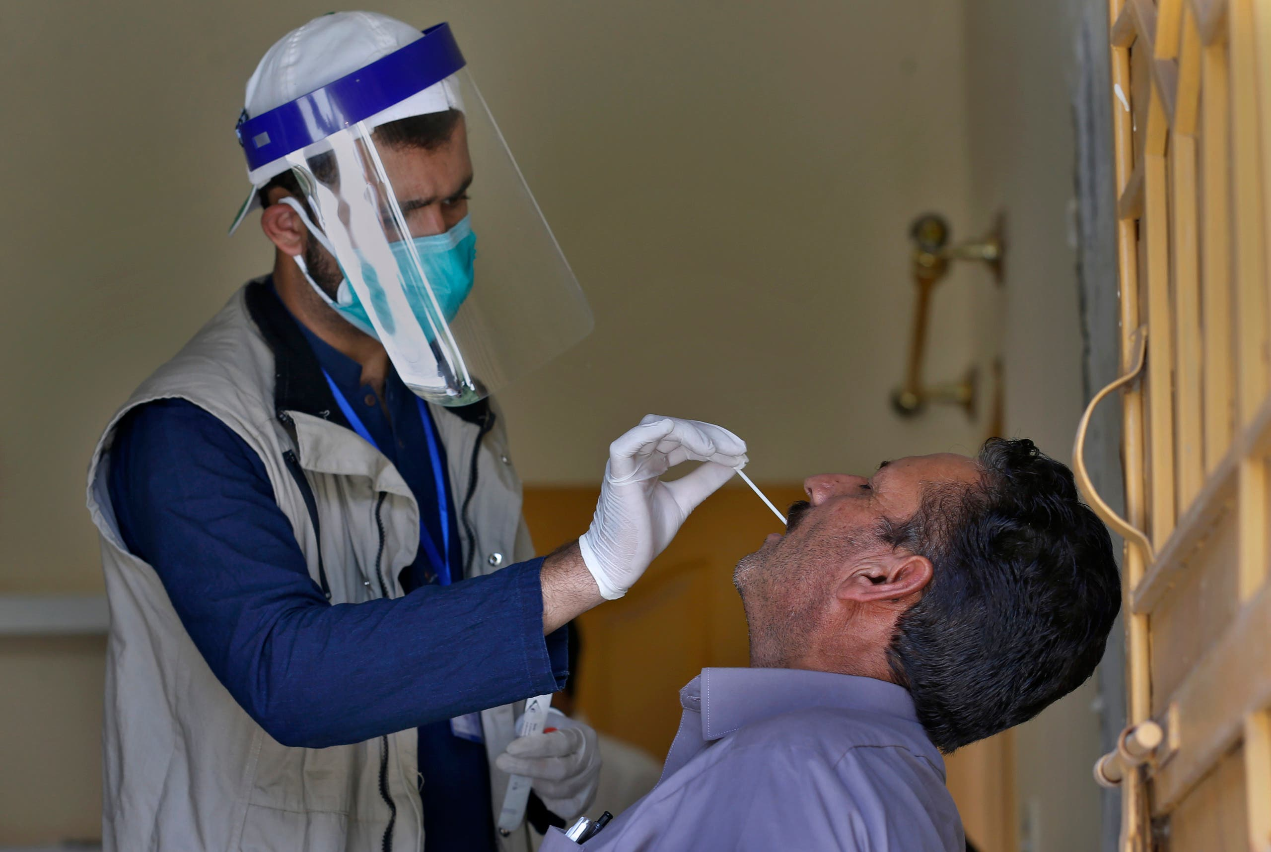 A health worker takes a swab sample of a person during door-to-door testing and screening facility for the new coronavirus, in Islamabad, Pakistan, Monday, June 15, 2020. (AP)