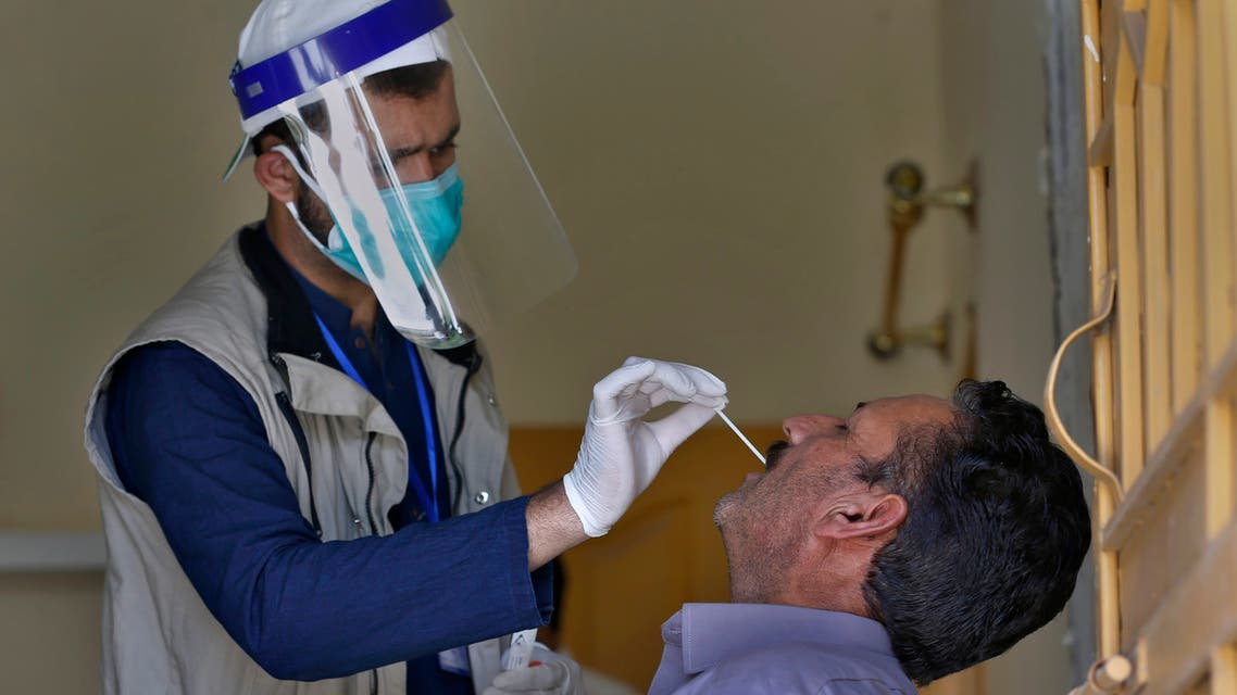 A health worker takes a nasal swab sample of a person during door-to-door testing and screening facility for the new coronavirus, in Islamabad, Pakistan, Monday, June 15, 2020. (AP)
