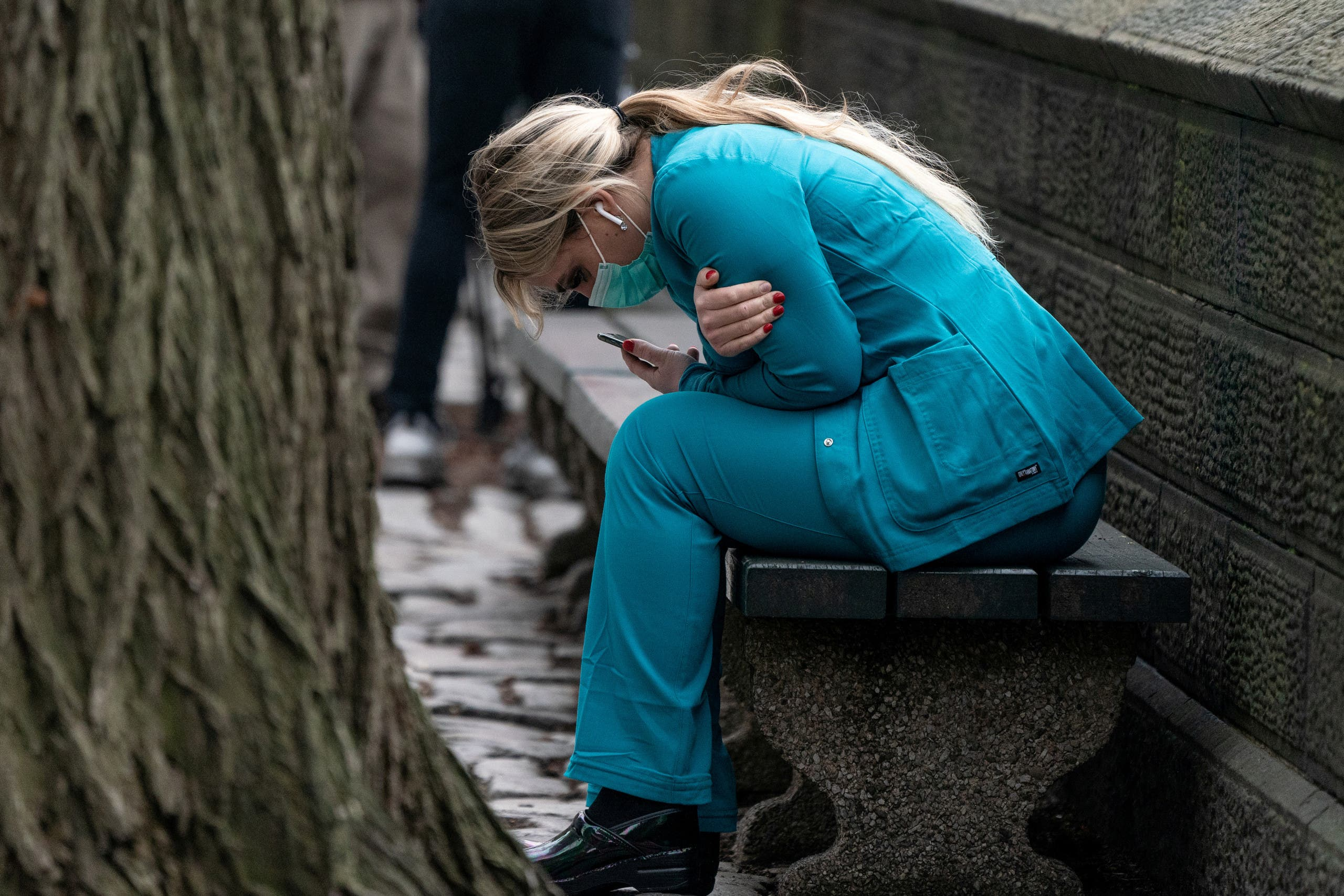 A healthcare worker sits on a bench near Central Park in the Manhattan borough of New York City, US, March 30, 2020. (Reuters)