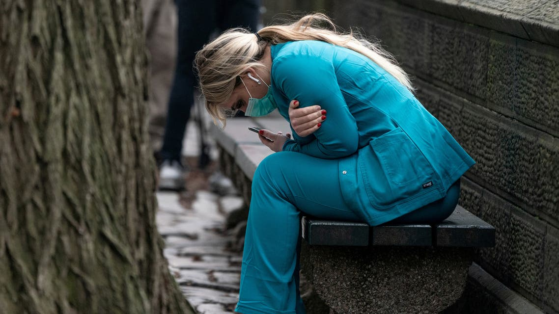 A healthcare worker sits on a bench near Central Park in the Manhattan borough of New York City, US, March 30, 2020. Reuters