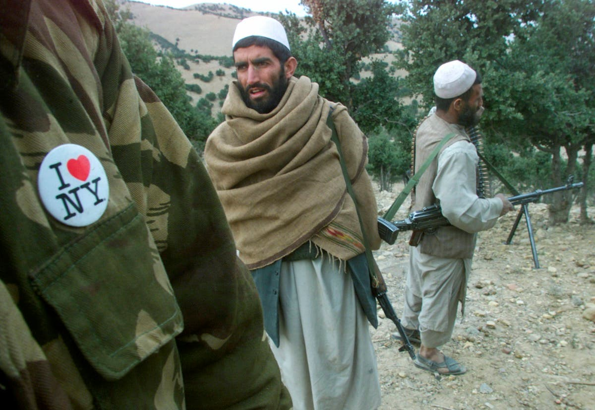 """An Afghan anti-Taliban fighter, wearing an """"I Love New York"""" button on his military jacket, stands among fellow fighters in the White Mountains near Tora Bora, Afghanistan. (AP)"""