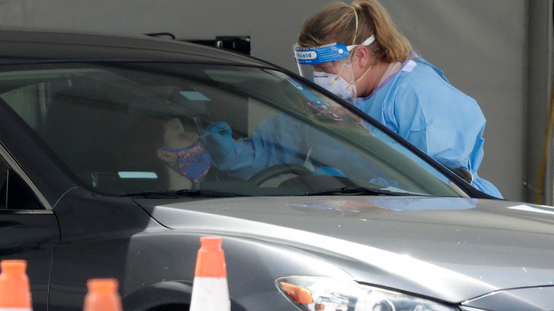 A healthcare worker takes a swab sample from a driver at a drive-through coronavirus testing site outside of Hard Rock Stadium, Friday, June 26, 2020, in Miami Gardens, Fla. (AP)