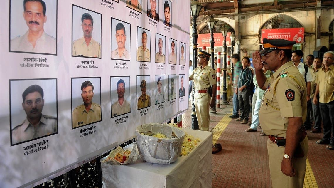 An Indian police officer pays his respects to police and uniformed personnel who lost their lives in 2008 terror attacks outside a railway station in Mumbai on November 26, 2012. (AFP)