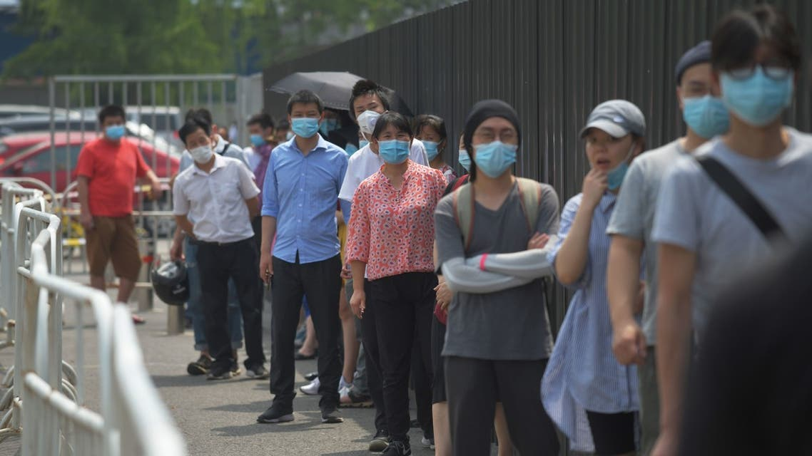 People wear masks as they wait in line to undergo COVID-19 coronavirus swab tests at a testing station in Beijing on June 28, 2020. Beijing has partially lifted weeks-long lockdown imposed in the Chinese capital to head off a feared second wave of coronavirus infections after three million samples were taken in two weeks, officials said. Dozens of residential compounds across the city were shut down, with authorities rolling out a mass testing campaign to root out any remaining cases.