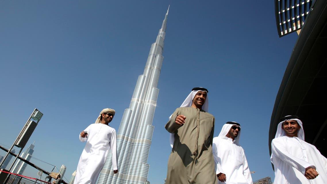 Emirati men walk past the Burj Khalifa, January 4, 2010. (Reuters)