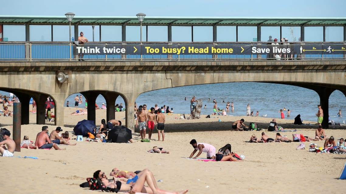 People relax on a beach enjoying the weather in Bournemouth, following the outbreak of the coronavirus disease (COVID-19), Bournemouth, Britain, May 26, 2020. (Reuters)