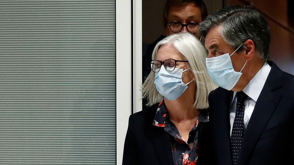 Former French prime minister Francois Fillon and his wife Penelope, wearing protective face masks, leave following the verdict in their trial over a fake jobs scandal at the courthouse in Paris, France, June 29, 2020. REUTERS/Gonzalo Fuentes