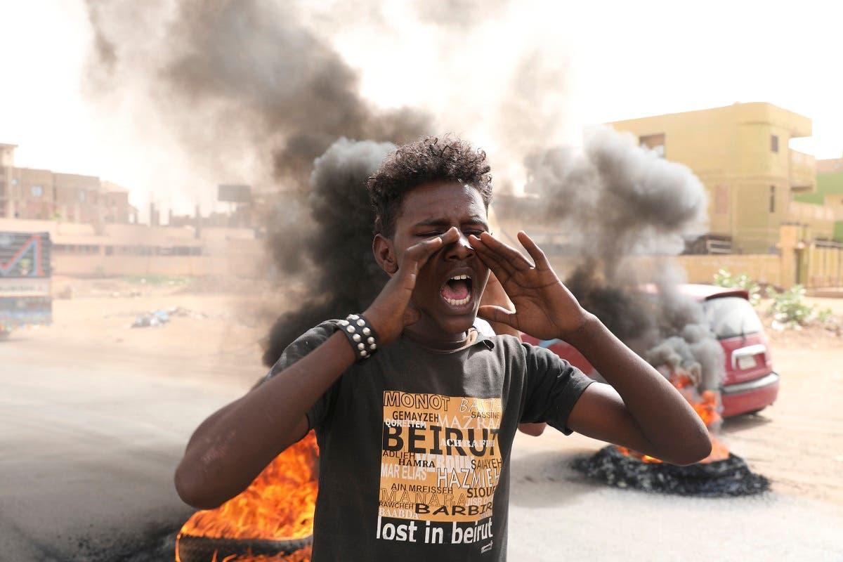 Sudanese men burn tires during a demonstration to commemorate the first anniversary of a deadly crackdown carried out by security forces on protesters during a sit-in outside the army headquarters, in Khartoum. (AP)