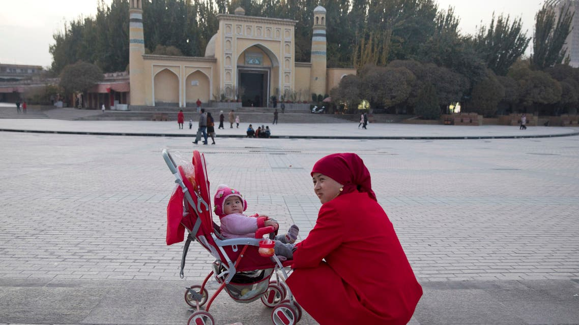 A woman tends to her child near the Id Kah Mosque in Kashgar in western China's Xinjiang region. (AP)