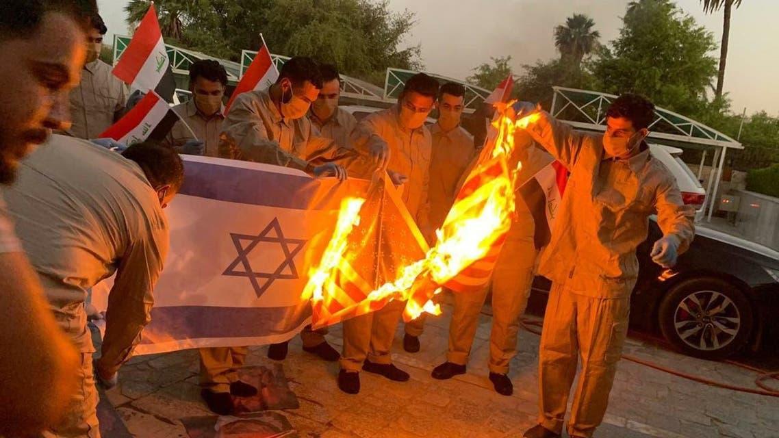 Detained Kata'ib Hezbollah fighters burn US flag upon release. (Photo via @iraqitweet/Twitter)
