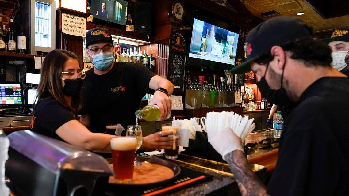 Jessica Ciaramitaro, Daryn Feenstra and Nicholas Soriano mix drinks while wearing face masks at the bar at San Pedro Brewing Company on Friday, May 29, 2020, in the San Pedro area of Los Angeles. (AP)