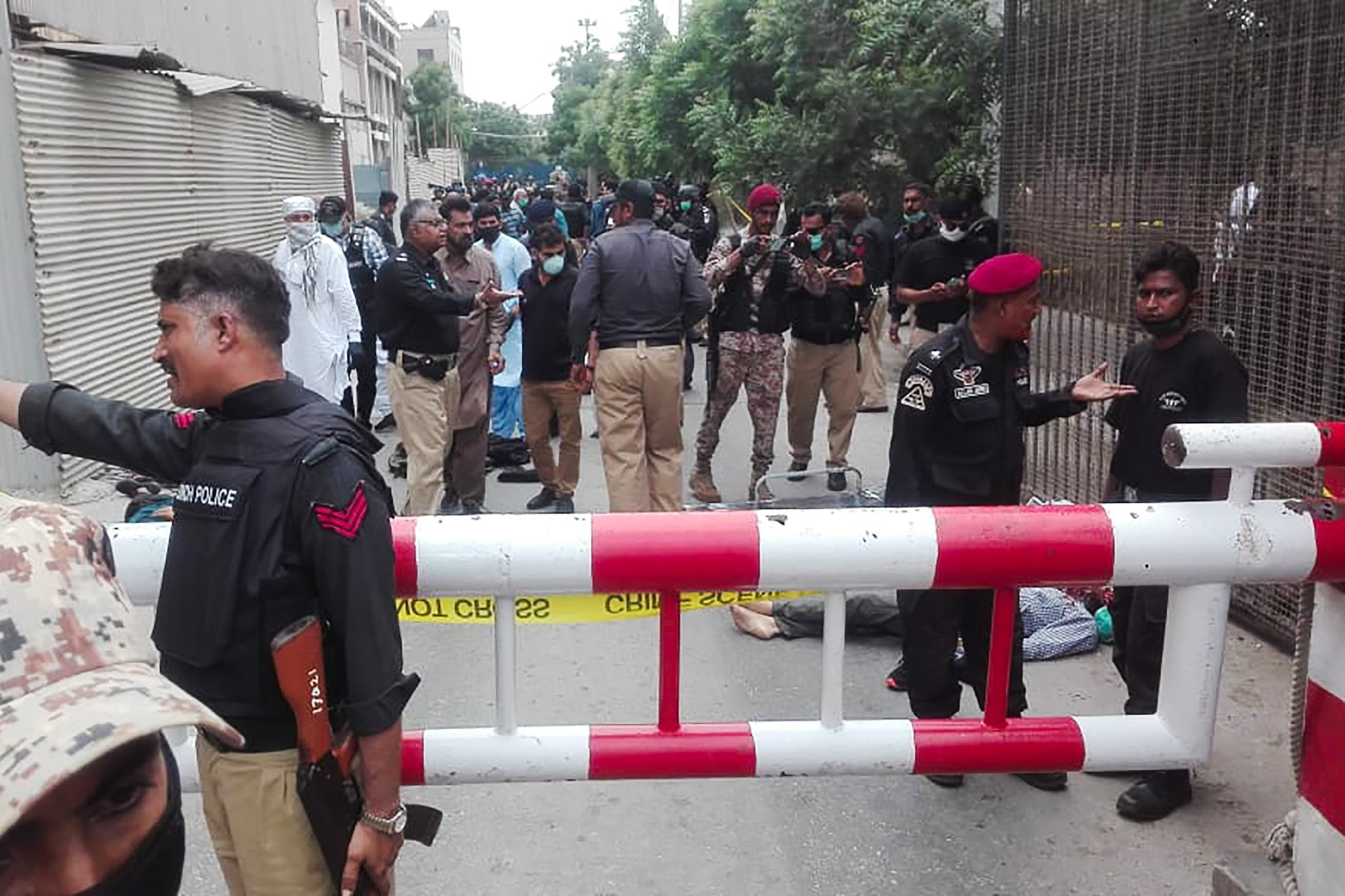 Policemen secure an area around a body outside the Pakistan Stock Exchange building after a group of gunmen attacked the building in Karachi. (AFP)