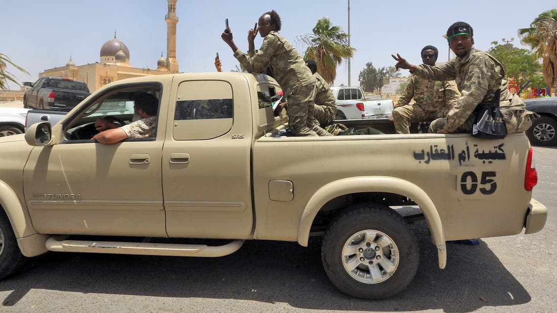 Fighters loyal to Libya's UN-recognised Government of National Accord (GNA) pose for a picture as they sit in the back of a pickup truck in the town of Tarhuna, about 65 kilometres southeast of the capital Tripoli on June 5, 2020, after the area was taken over by pro-GNA forces from rival forces loyal to strongman Khalifa Haftar. The GNA said on June 5 that it was back in full control of Tarhouna, the last stronghold of the forces of eastern strongman Khalifa Haftar. The UN-recognised government had announced the day before that they were also in full control of the capital Tripoli and its surroundings.
