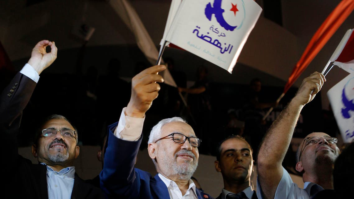 Rached Ghannouchi, leader of the Islamist party Ennahda, waves the party flag outside Ennahda's headquarters in Tunis October 27, 2014.Tunisia's Ennahda party, the first Islamist movement to secure power after the 2011 Arab Spring revolts, conceded defeat on Monday in elections that are set to make its main secular rival the strongest force in parliament. Official results from Sunday's elections - the second parliamentary vote since Tunisians set off uprisings across much of the Arab World by overthrowing autocrat Zine El-Abidine Ben Ali - were still to be announced. REUTERS/Zoubeir Souissi (TUNISIA - Tags: ELECTIONS POLITICS)