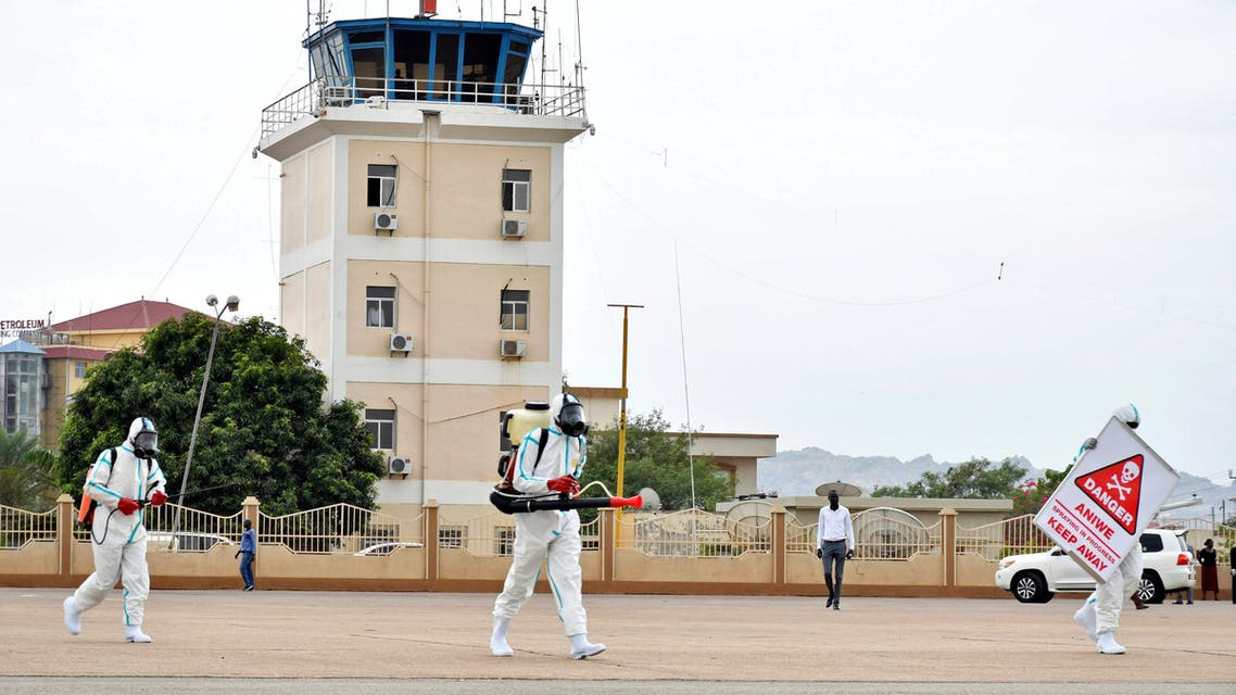 Members of a medical team wearing protective suits clean the airfield, to prevent the spread of the coronavirus disease (COVID-19), at the Juba International Airport in Juba. (Reuters)