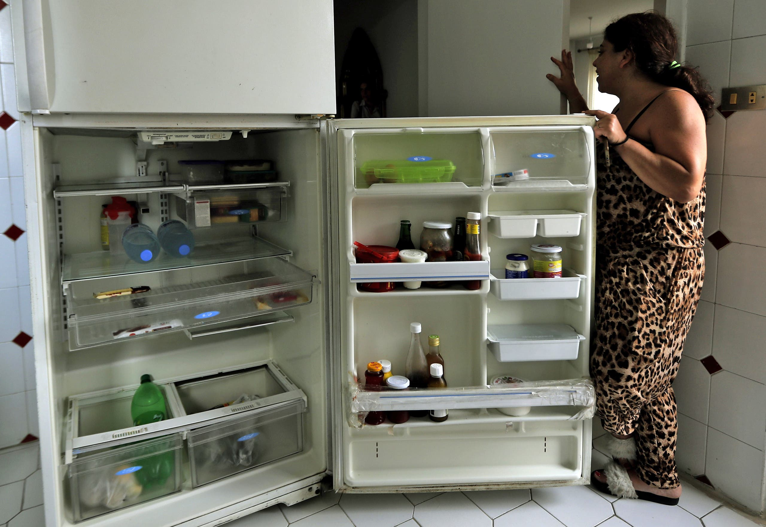 A Lebanese woman displays the content of her refrigerator at her apartment in Jounieh, north of the capital Beirut, on June 19, 2020. (AFP)