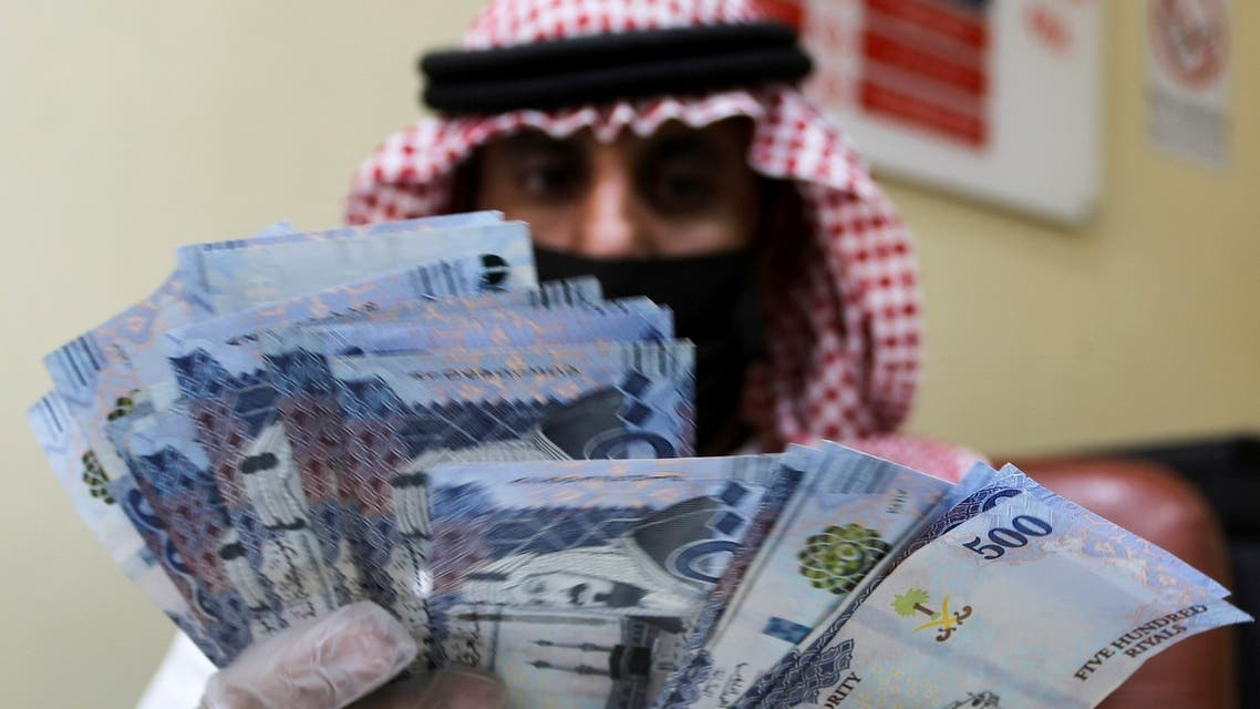 A Saudi money exchanger wears gloves as he counts Saudi riyal currency at a currency exchange shop in Riyadh, Saudi Arabia, March 10, 2020. (Reuters)