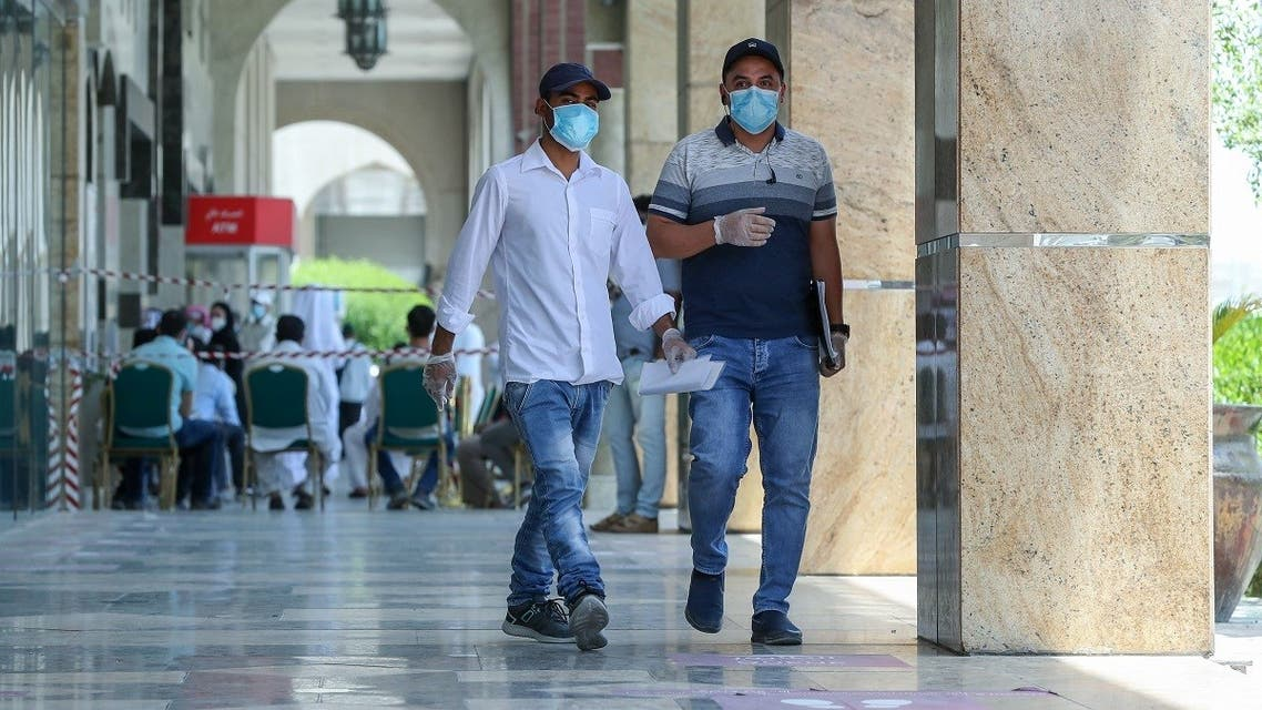 People wearing protective gear walk by on a street of Qatar's capital Doha, on May 17, 2020. (AFP)