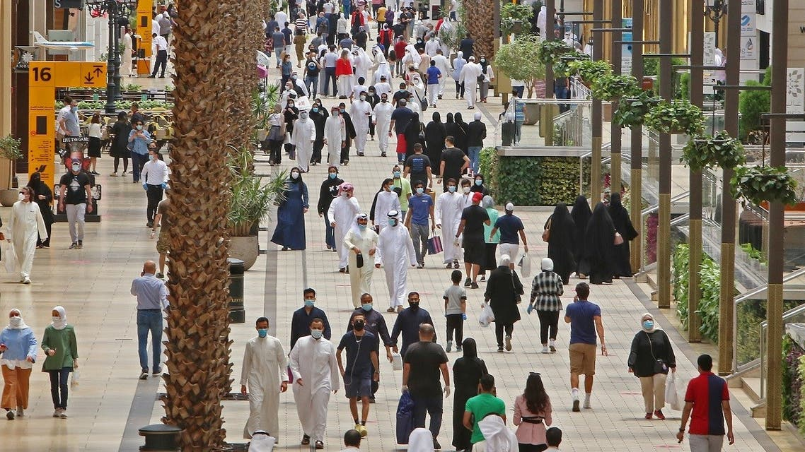 Kuwaitis wearing face masks walk inside the re-opened Avenues Mall, the country's largest shopping centre, on June 30, 2020 in Kuwait City. (AFP)