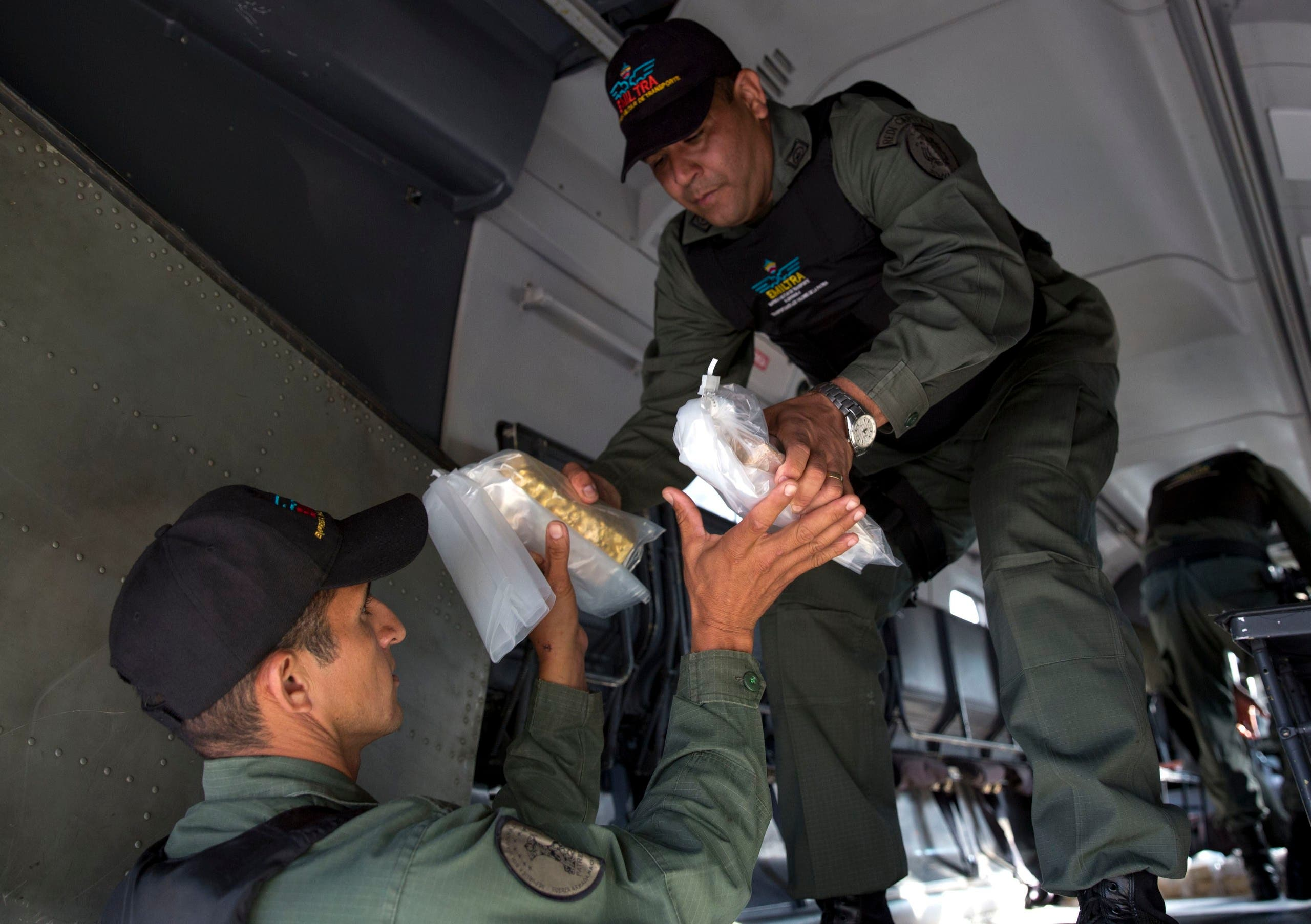 Military personnel remove gold bars from a military plane to be taken to Venezuela's Central Bank, at the Carlota military airport in Caracas on March 1, 2018. (AP)
