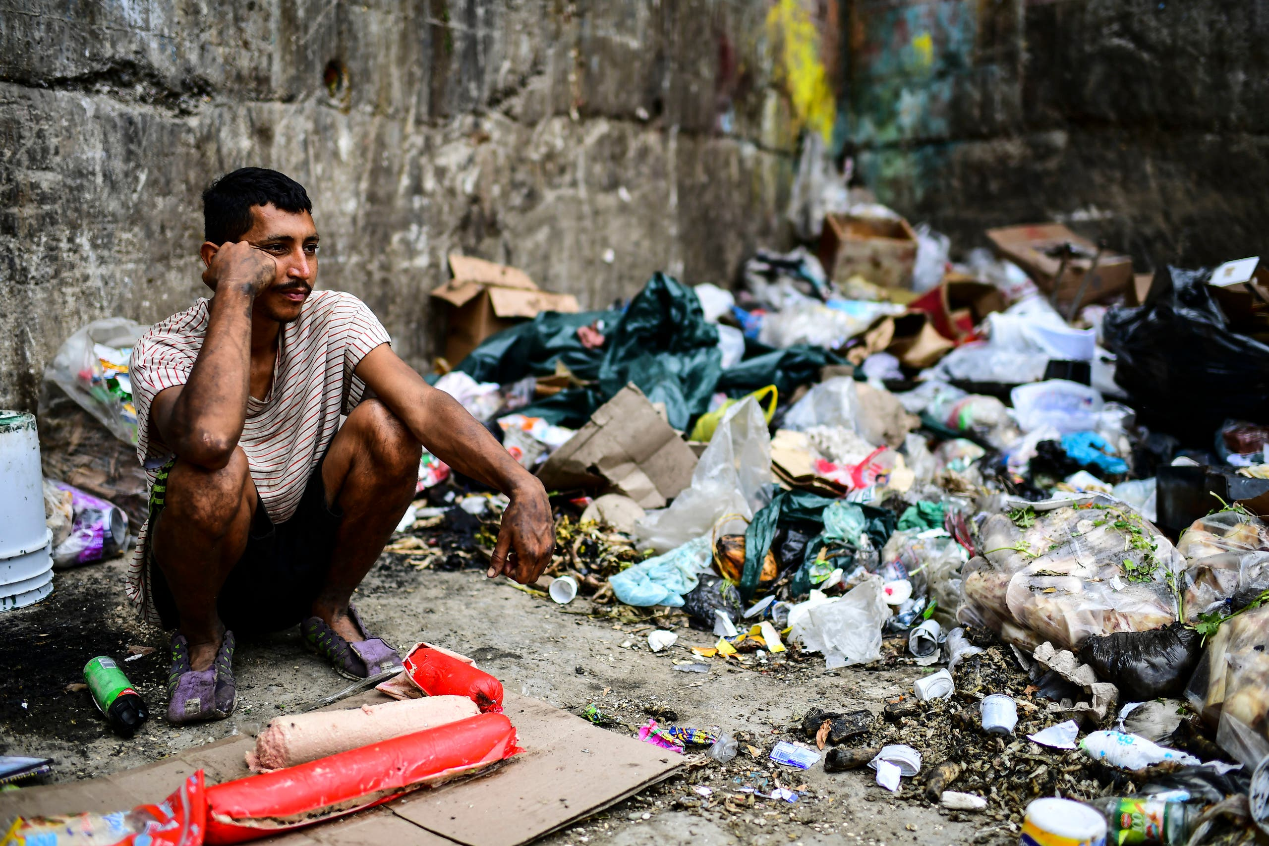 A man waits to get some food at a garbage dump in Las Minas de Baruta neighborhood, Caracas, Venezuela, on March 14, 2019. (AFP)