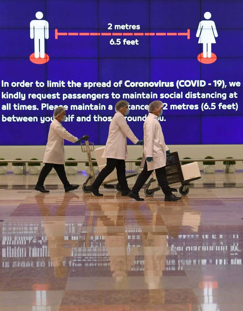 Employees at Dubai International Airport, walk past a poster reminding passengers to keep a safe distance from each other, after the resumption of scheduled operations by Emirates airline, amid the coronavirus pandemic, on May 22, 2020. (AFP)