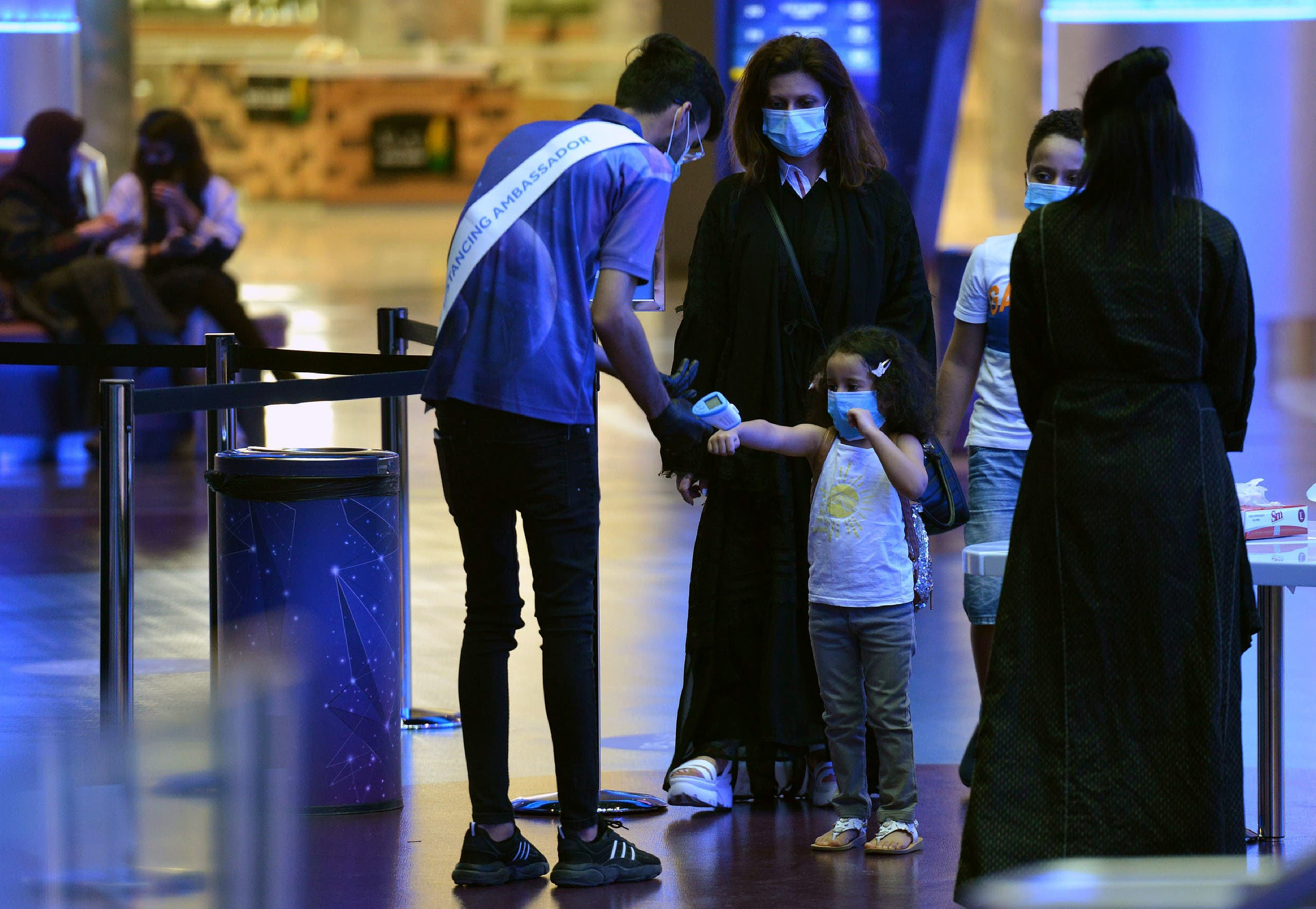 A man measures the temperature of a child as a family enter a movie theatre at a cinema in the Saudi capital Riyadh, on June 22, 2020 as cinemas re-opened following the lifting of a lockdown due to the COVID-19 coronavirus pandemic. (File photo: AFP)