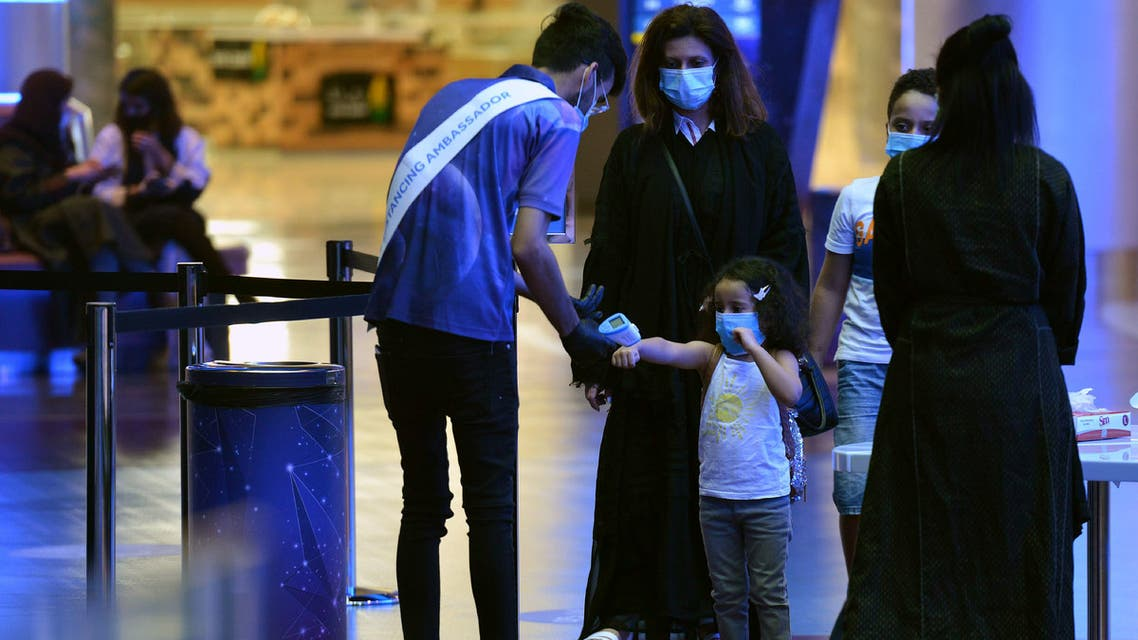 A man measures the temperature of a child as a family enter a movie theatre at a cinema in the Saudi capital Riyadh, on June 22, 2020 as cinemas re-opened following the lifting of a lockdown due to the COVID-19 coronavirus pandemic.