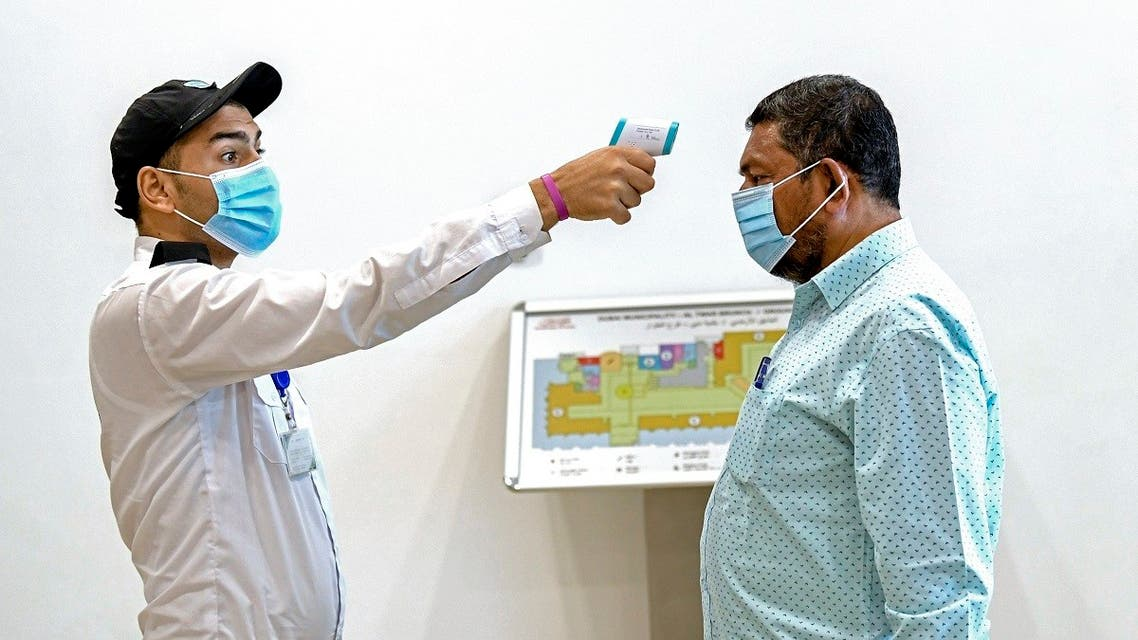 An Emirati security guard checks a visitor's temperature at the Passports Department as civil servants return to work following the easing of restrictions in Dubai on 16 June, 2020. (AFP)