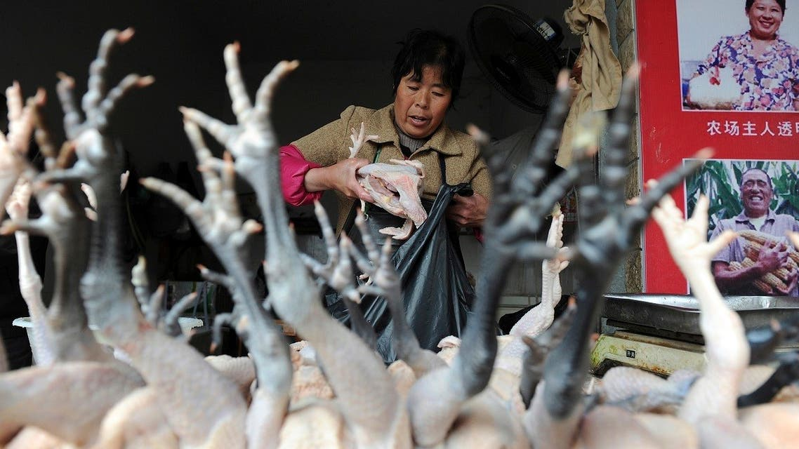 A vendor puts chickens into a plastic bag at a poultry market in Hefei, Anhui province, April 3, 2013.  (Reuters)