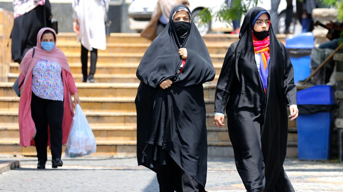 Pedestrians wearing protective masks due to the COVID-19 coronavirus, walk along a street in the Iranian capital Tehran on June 28, 2020. Iran's President Hassan Rouhani said today that mask-wearing will be mandatory in certain areas as of next week and gave virus-hit provinces the green light to reimpose restrictive measures.