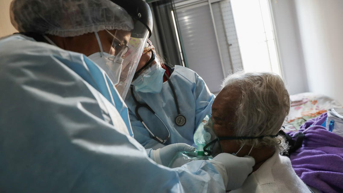 Maria Geralda da Silva, 84, who is experiencing breathing difficulty and others symptoms of the coronavirus disease (COVID-19), receives oxygen from Emergency Rescue Service's (SAMU) Belisa Marcelino and Cristina Almeida as preparation is done to transfer her to a hospital for treatment amid the outbreak, in Sao Paulo, Brazil, July 2, 2020. REUTERS/Amanda Perobelli