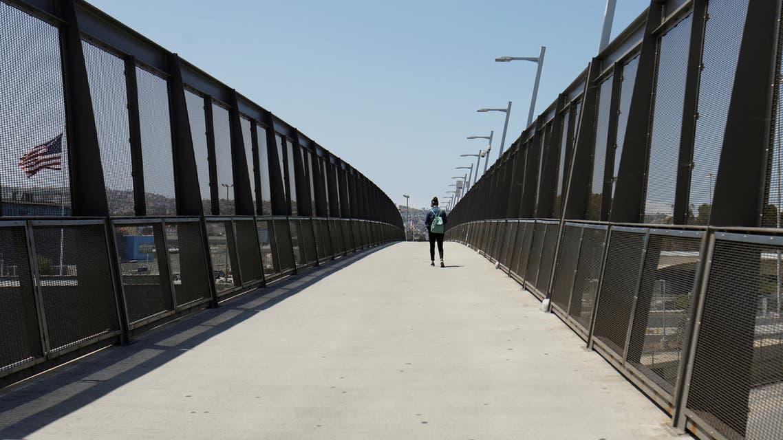 FILE PHOTO: A lone pedestrian walks across the pedestrian bridge at the U.S.-Mexico border during the coronavirus disease (COVID-19) outbreak in San Diego, California, U.S., April 21, 2020. REUTERS/Mike Blake - RC289G9G101X/File Photo