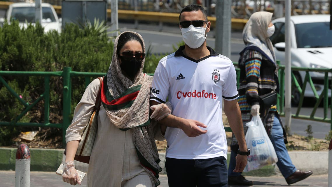 Pedestrians wearing protective masks due to the COVID-19 coronavirus, cross a street in the Iranian capital Tehran on June 28, 2020. Iran's President Hassan Rouhani said today that mask-wearing will be mandatory in certain areas as of next week and gave virus-hit provinces the green light to reimpose restrictive measures.