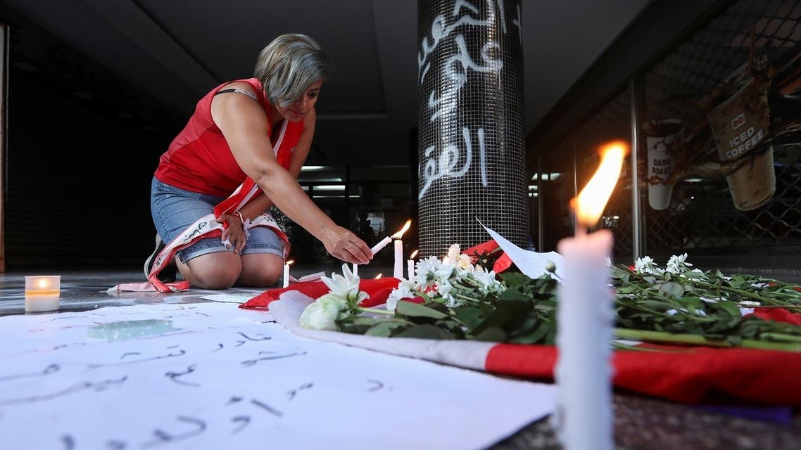A woman lights a candle at the site where a man killed himself in Beirut, Lebanon. (Reuters)