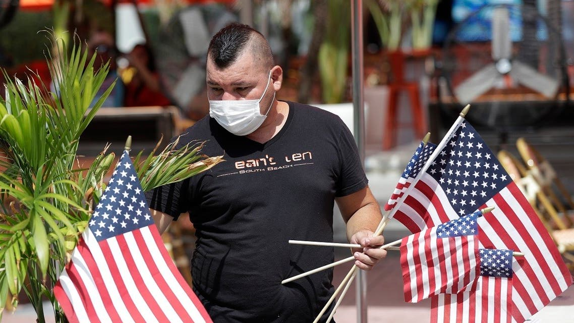 Marvin Turcios puts out American flags at Ocean's 10 restaurant on Miami Beach, Florida's famed Ocean Drive on South Beach. (AP)