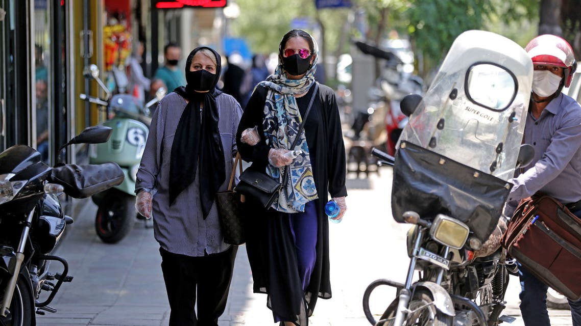 Iranian pedestrians wearing protective masks due to the COVID-19 pandemic, walk along a street in the capital Tehran on July 1, 2020.