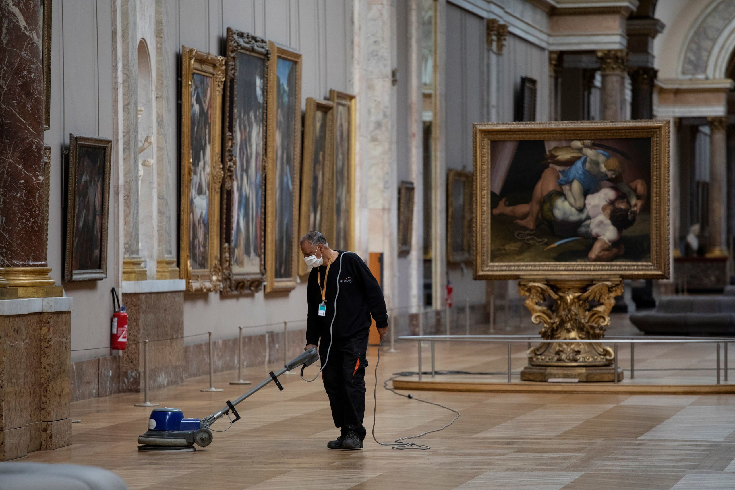 An employee cleaning the floor of a room of the Musee du Louvre in Paris. (AFP)