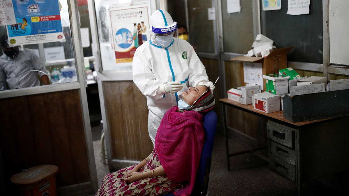 A health worker in personal protective equipment (PPE) collects a sample using a swab from a girl at a local health centre to conduct tests for the coronavirus disease (COVID-19), amid the spread of the disease, in New Delhi, India July 4, 2020. REUTERS/Adnan Abidi