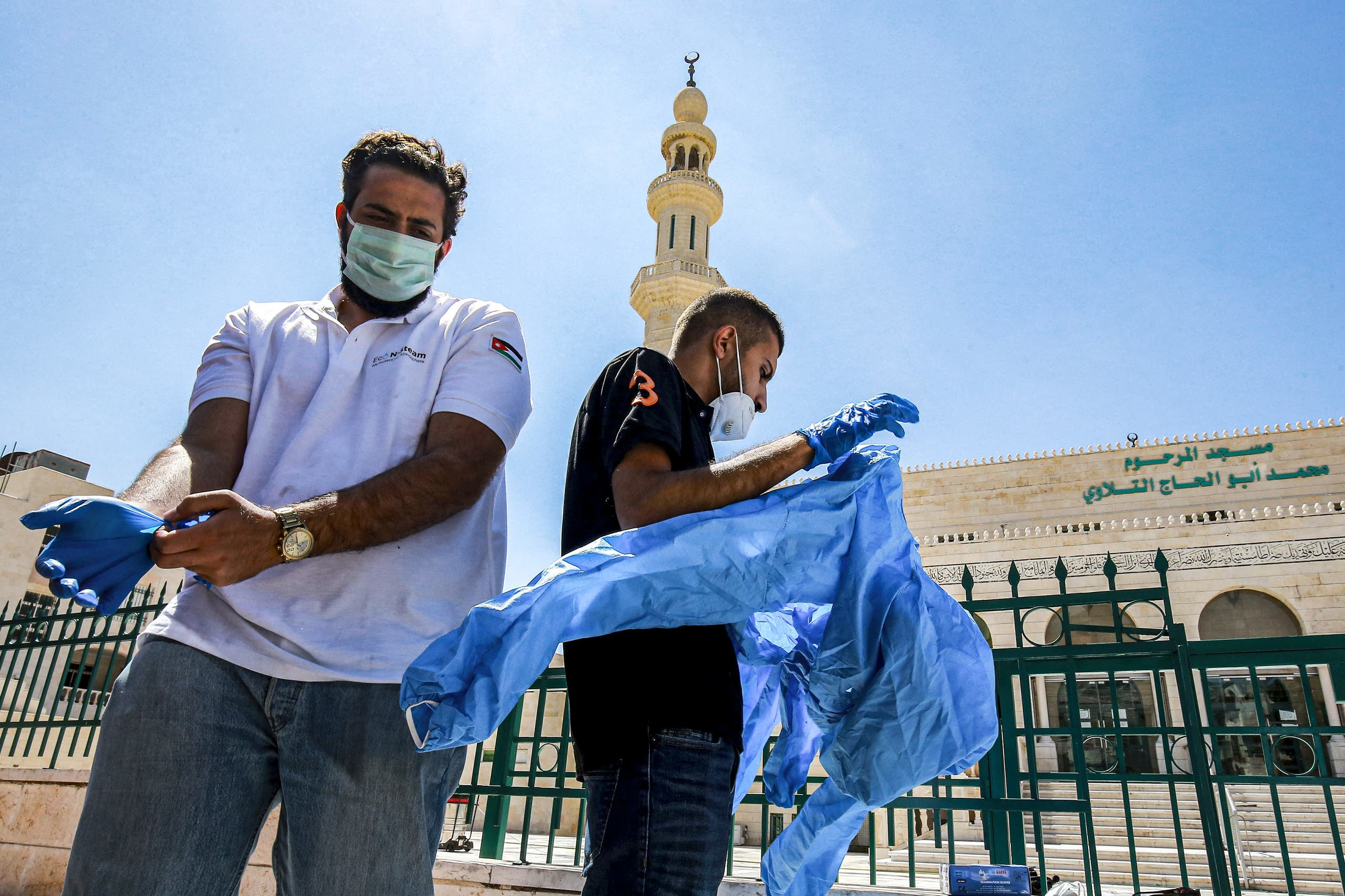 Workers suit up in PPE (personal protective equipment) before sterilizing a mosque in Jordan's capital Amman on June 3, 2020. (AFP)