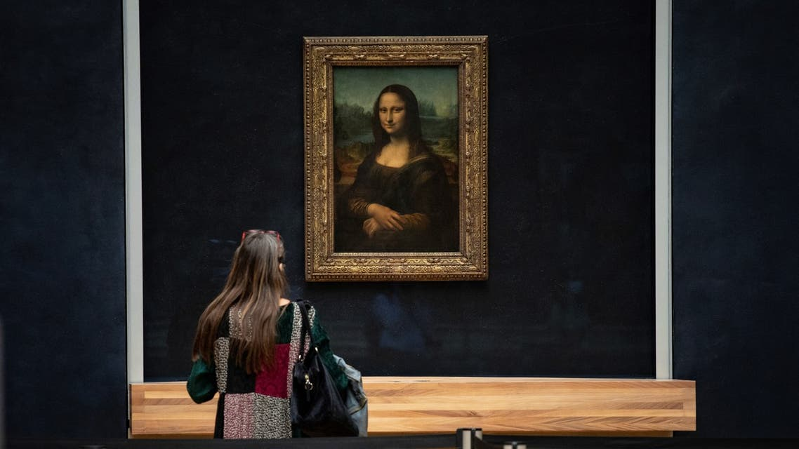 a woman in front of Italian artist Leonardo da Vinci's Mona Lisa at the Louvre in Paris, during a press visit of the museum. (AFP)