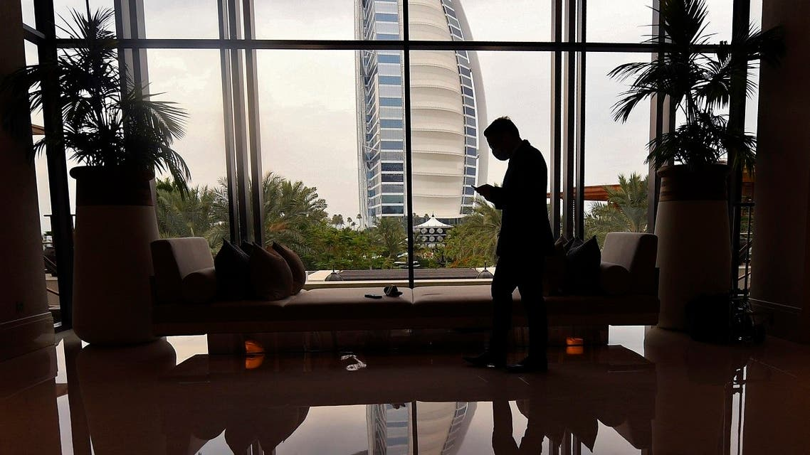 A mask-clad staff member of the Jumeirah al-Naseem hotel walks past a window while behind him is seen the Burj Al Arab hotel. (Reuters)