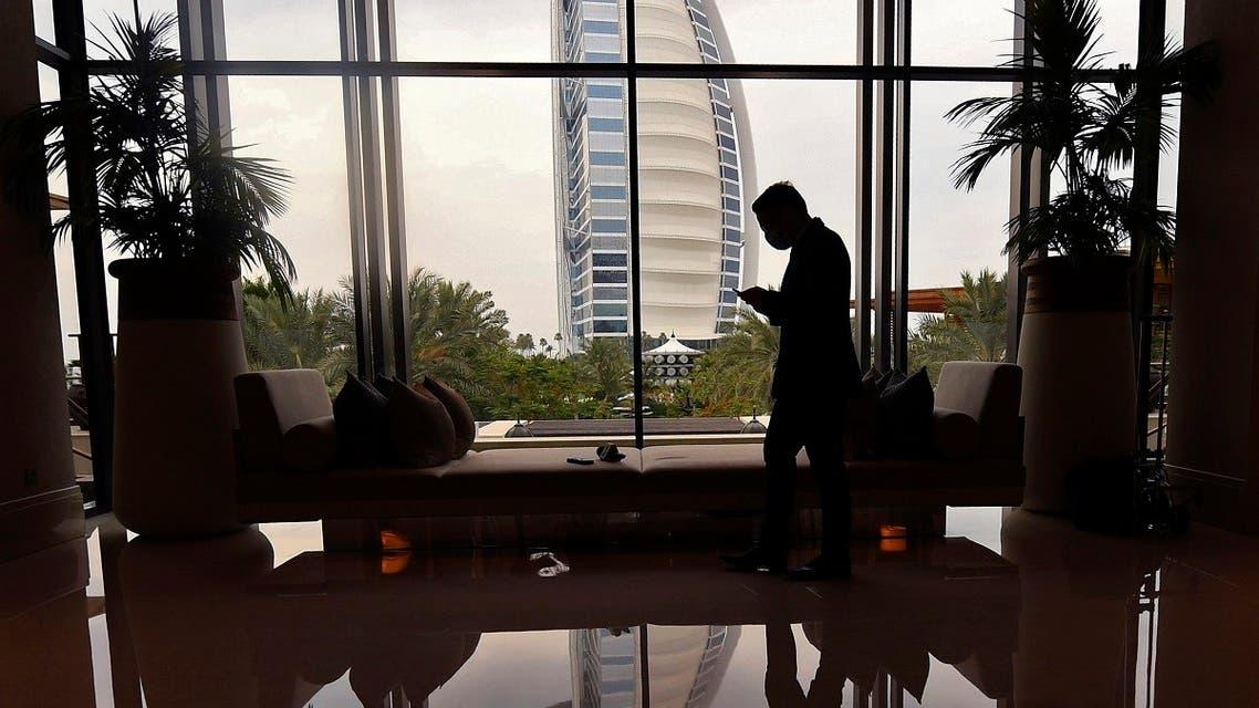 A mask-clad staff member of the Jumeirah al-Naseem hotel walks past a window while behind him is seen the Burj Al Arab hotel. (Reuters)