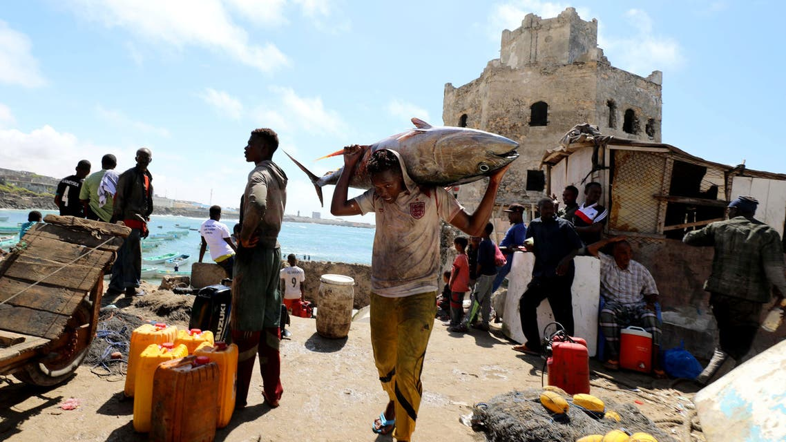 A fisherman carries his catch in front of buildings, destroyed during a war, in Hamarweyne district near a fishing port in Mogadishu, Somalia September 14, 2018. (Reuters)