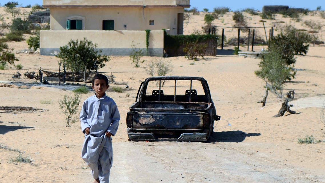 An Egyptian child walks in front of the wreckage of a burnt down car, the day after an attack by Egyptian Army in a village on the outskirt of the Northern Sinai town of Sheik Zuweid on September 10, 2013 in Egypt. A series of attacks in Egypt's restive Sinai peninsula over the past 24 hours, mostly against soldiers, killed at least four people, security officials said. The violence comes as the Egyptian military presses its campaign in Sinai to quell an insurgency that surged after the army overthrew Islamist president Mohamed Morsi on July 3. AFP PHOTO/MOHAMED EL-SHAHED